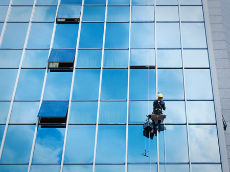 Photo for Window cleaner working on a glass facade suspended. Heavy work concept - Royalty Free Image