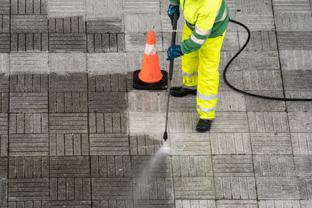 Photo pour Worker cleaning the street sidewalk with high pressure water jet. Public maintenance concept - image libre de droit