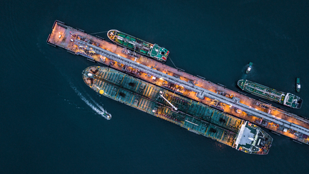 Photo for Aerial view of oil tanker ship at the port, Aerial view oil terminal is industrial facility for storage of oil and petrochemical products ready for transport to further storage facilities. - Royalty Free Image
