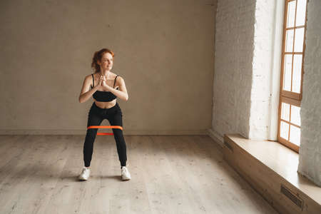 Photo pour Woman training with resistance bands at health club. Sporty attractive female working out - image libre de droit