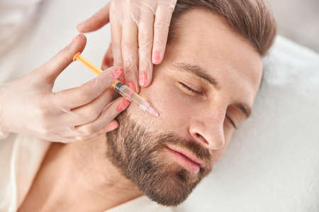 Photo pour Close up makes mesotherapy injections to young man. Treatment of male by a beautician for tightening and smoothing wrinkles on the face skin - image libre de droit
