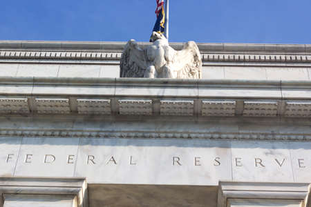 Federal Reserve building in Washington DC, US. Close up of a top part of the building with eagle statue.