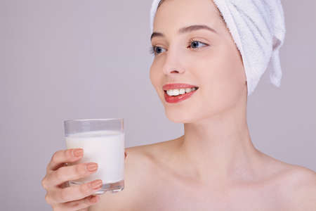 Photo pour A young girl with well-groomed skin in a white towel on her head holds a glass of milk in her hands. Proper nutrition. Healthy teeth. Calcium. Vegetable milk. - image libre de droit