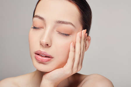 Foto de An elegant sophisticated beautiful girl with full lips, brown hair and clean delicate skin on the gray background. Lady put her head on her hand. Close eyes. Spa, face skin care. Wellness. - Imagen libre de derechos