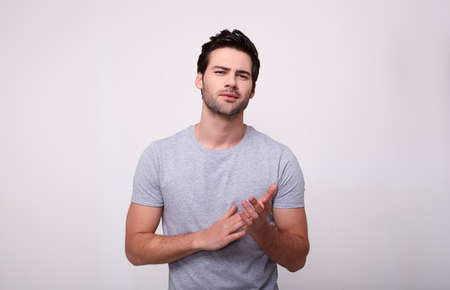 Photo pour Handsome young man in a gray t-shirt looking at camera, standing on gray background. - image libre de droit