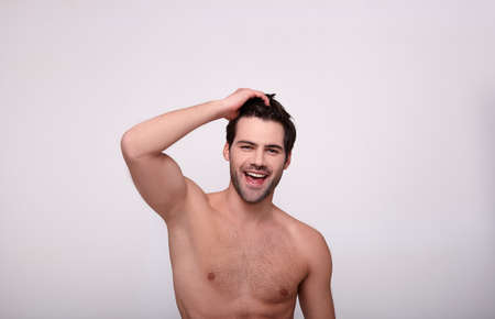 Photo pour Happy enthusiastic brutal handsome man touches his hair by right hand, smiles broadly and looks straight with open mouth. Copy space. - image libre de droit