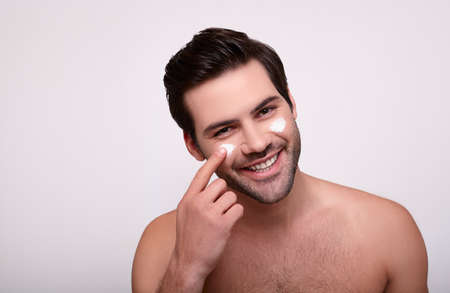 Photo for Beauty treatments and skin care. Close up portrait of a happy laughing topless man with cream, touching with his hand. Isolated over white background. Copy space. - Royalty Free Image