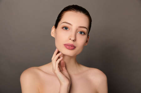 Photo pour Close up portrait of beautiful lady with perfect skin looking away and keeping hands on her cheeks. Isolated on gray background. - image libre de droit
