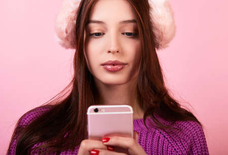 Photo pour Teenager dark-haired girl in a knitted sweater and fluffy pink headphones holding a phone. Looks at the phone. Photo on a pink background. Winter mood, winter clothes. New Year's bustle. - image libre de droit