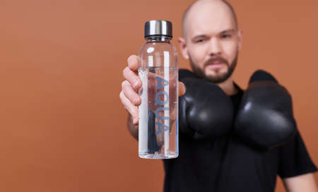 Photo pour Portrait of a charming smiling guy with a beard, in a black T-shirt, he after training on boxing, holding a water bottle with the inscription aqua. The concept of sports and water balance, lifestyle. - image libre de droit