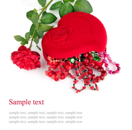 Red heart-shaped casket with beads of  semi-precious stones and rose  isolated on  white background