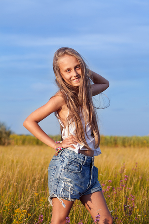 Beautiful little young fashionable hippie teenager girl in fashion clothing in a meadow  Summer day, outdoors