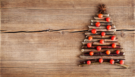 Christmas card with natural decorations on wooden background. Set of different varieties of objects in the form of a tree. Winter holidays concept