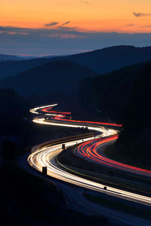 Long Exposure of Car Lights on Motorway Meandering through Hills at Sunset