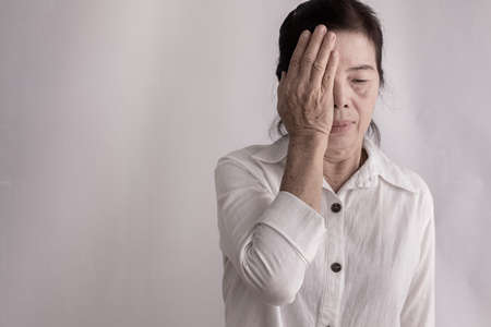 Foto de asian elderly woman having eye pain on isolated background, concept of healthy care lifestyle. - Imagen libre de derechos