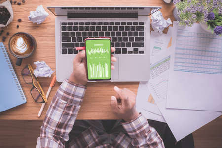 Photo pour businessman using mobile phone with mock up chart report on screen. office desk. - image libre de droit