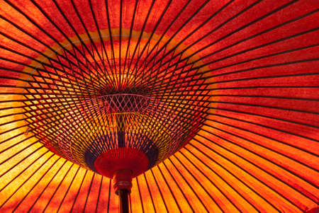 A closeup of a red, Japanese parasol from below with sun shining down