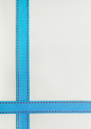 Foto de Blue Ribbon with red stitching over a textured background. - Imagen libre de derechos