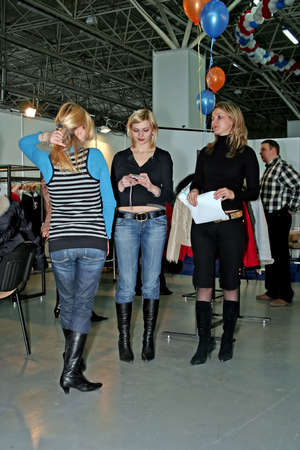 Three girls - managers on presentation of fashionable clothes.