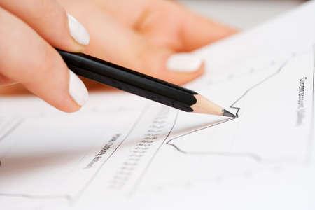 Female hand working witn financial documents.