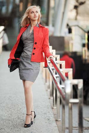 Photo pour Young businesswoman walking on the city street - image libre de droit
