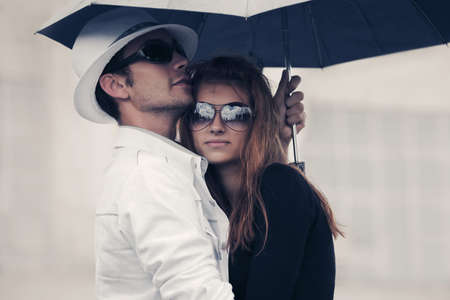 Photo pour Young fashion couple in love with umbrella Stylish man and woman embracing on city street - image libre de droit