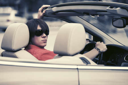 Foto de Young handsome man in sunglasses driving convertible car - Imagen libre de derechos