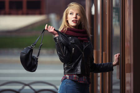 Photo pour Young fashion blonde woman with handbag at the mall doorway Stylish female model in black leather jacket and snood scarf - image libre de droit
