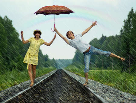 Young couple under rain on railroad track
