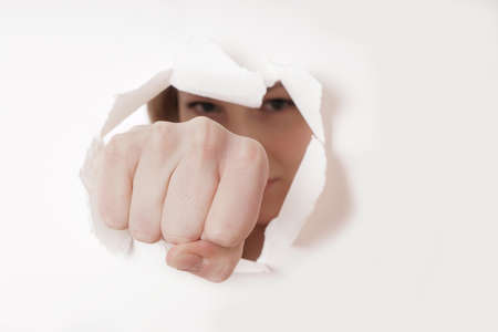 woman punching hole through paper wall with fist