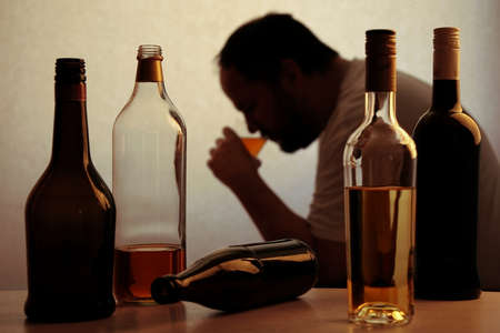 Photo for silhouette of anonymous alcoholic person drinking behind bottles of alcohol - Royalty Free Image