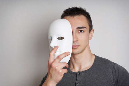Photo for young man taking off plain white mask revealing face - Royalty Free Image