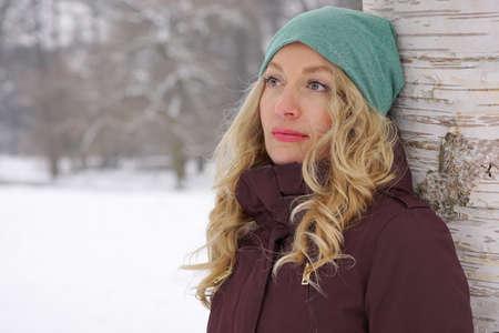 Photo pour pensive woman leaning against birch tree in snow covered winter landscape - image libre de droit