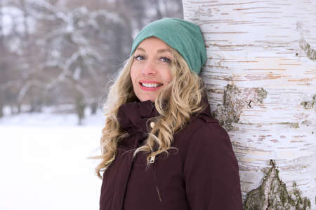 Photo pour smiling woman leaning against birch tree in snow covered winter landscape - image libre de droit