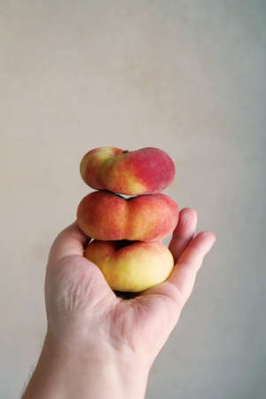 male hand holding stack of flat peaches also known as saturn donut or doughnut peach