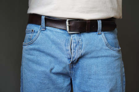 Photo pour midsection of unrecognizable man dressed in jeans with open fly or flies or zipper - image libre de droit