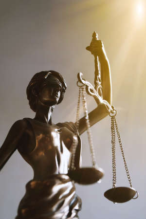Photo pour lady justice or justitia blindfolded figurine holding balance scales - law and legal symbol - with sun rays light leak - image libre de droit