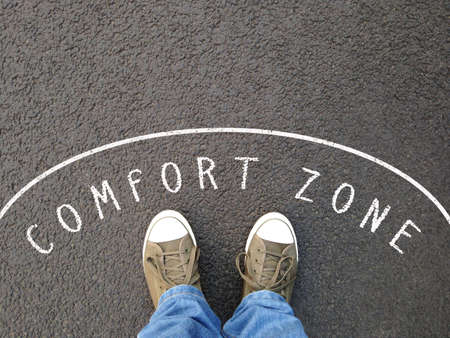 Photo for feet in canvas shoes standing inside comfort zone - foot selfie from personal perspective - chalk text on asphalt - Royalty Free Image