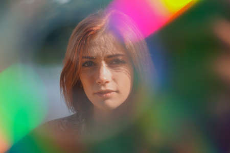 funky colorful portrait of a young woman with lens flare and light leaks - authentic real people creative portraiture