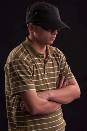 Serious young caucasian man with sunglasses and baseball hat, looks down