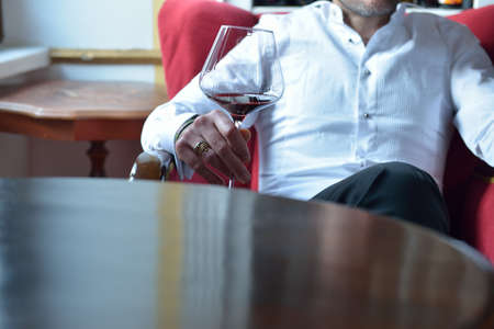 Bridegroom in a white shirt standing with a glass of wine in his hand, sitting at a wooden table, waiting with great emotions for his beautiful bride. Selective focus. Lights and shadows