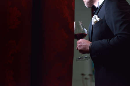 Stylish bridegroom in a beautiful black suit standing with a glass of wine in his hand, after a purple curtain, waiting with great emotions for his beautiful bride. Selective focus. Lights and shadows