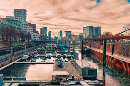Foto de DUESSELDORF, GERMANY - JANUARY 20, 2017: The marina on the other side of the New Media Harbor hosts private and commercial vessels. - Imagen libre de derechos
