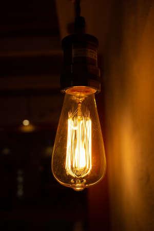 Photo for Golden shining antique Edison style bulb in the dark. Lighting decor concept. Vintage light bulb - Royalty Free Image