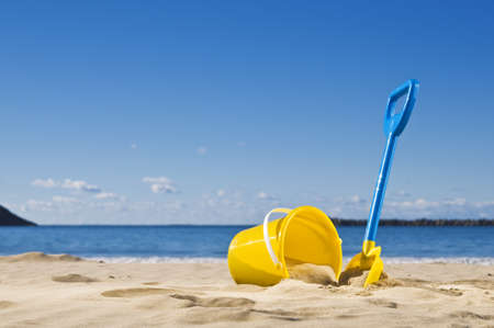 Spade and bucket by the water's edge, ready to build a sandcastle.
