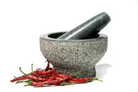 Fresh red chillies with pestle and mortar, isolated on a white background.