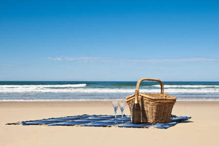 Picnic blanket,champagne,picnic basket and a beautiful tropical beach
