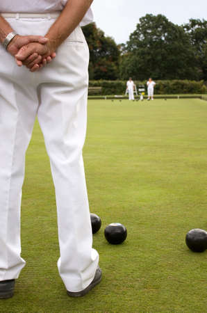 People dressed in white playing bowls on a bowling green