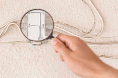 Photo for A worker's hand inspects a large antenna splitter with a magnifying glass, close-up. - Royalty Free Image