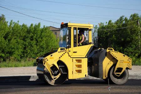 Yellow rolling machinery paving asphalt at summer